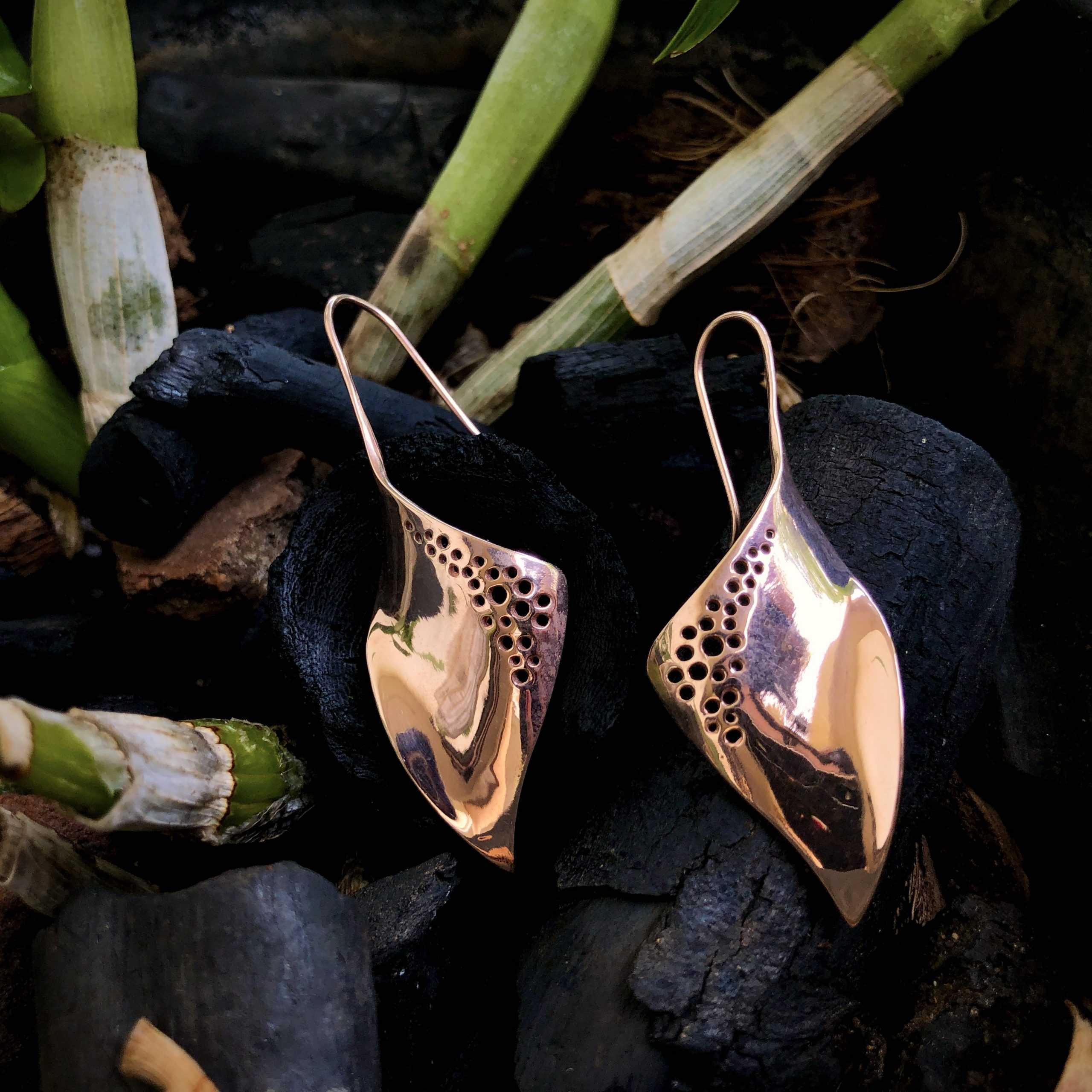 image showing ribelli's Rose gold plated sterling silver earrings with filigree work on a contrasting background of natural items