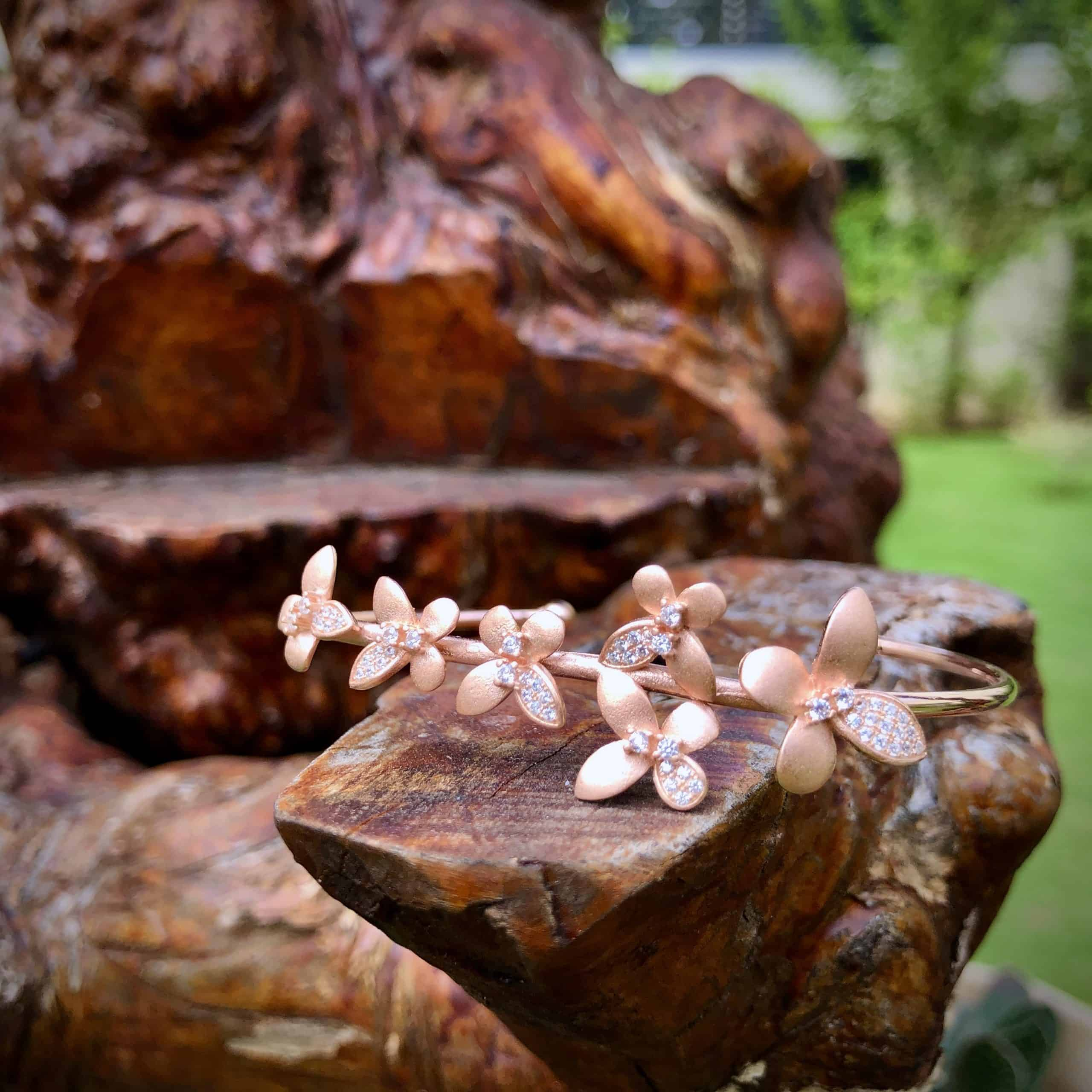 Image showing rose gold plated sterling silver bracelet with small flowers studded with American diamonds on a wooden stand