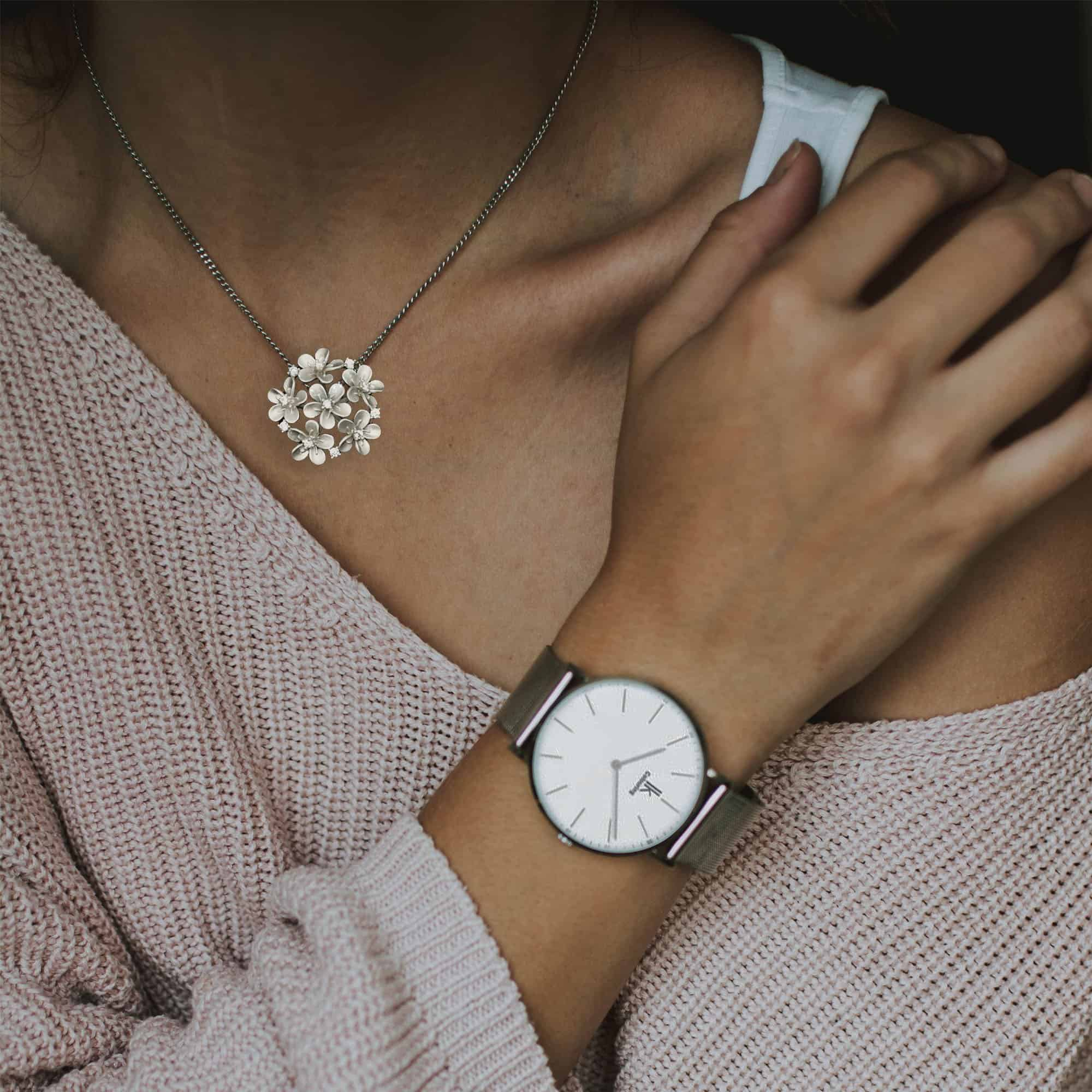 Image showing model wearing Ribelli's sterling silver pendant shaped like a bunch of small flowers studded with American diamonds.